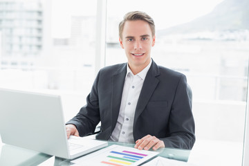 Smiling young businessman with laptop at office desk