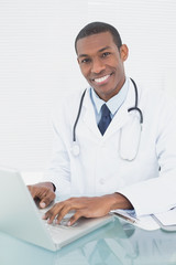Smiling doctor using laptop at medical office