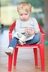 Girl sits on plastic chair reading children book about animals