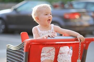 Happy little girl sitting inside shopping cart