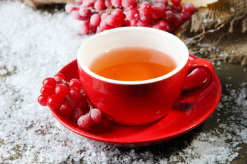 Still life with viburnum  tea in cup, berries and snow,