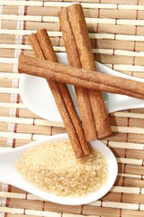 cinnamon sticks with cane sugar on white ceramic spoon
