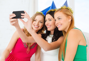three smiling women in hats having fun with camera
