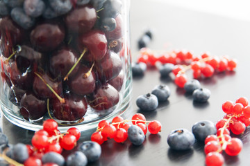 Blueberry, cherry and redcurrant in big glass on dark wood table