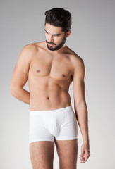 sexy handsome naked man in underwear posing in the studio