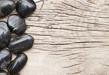 black stones on a old wooden background