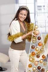 Laughing beauty decorating christmas tree