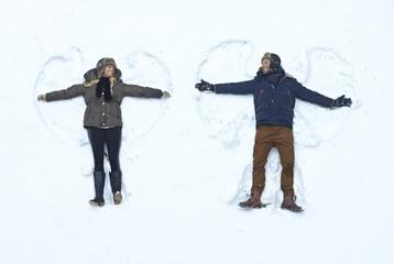 Loving couple making snow angel