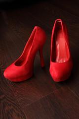 Rote Damenschuhe auf Holzboden