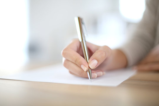Closeup of woman's hand writing on paper