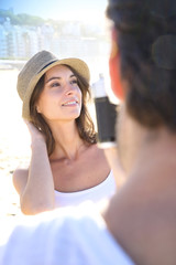Man taking picture of beautiful woman at the beach