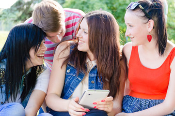Four happy teen friends laughing on picture of themselves
