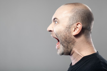 portrait of angry man screaming isolated on gray background with Wall mural