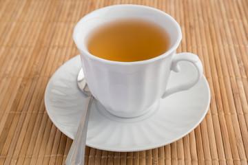 A cup of green tea on bamboo mat