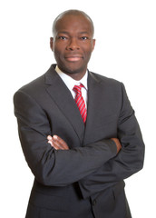 Smiling african businessman with crossed arms in black suit