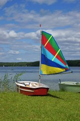 Sailing, sailboat Optimist with colored sail