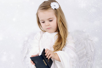 A beautiful little girl angel with a book
