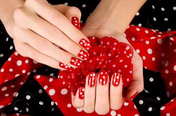 Close up on female hands with cute red manicure with white dots.