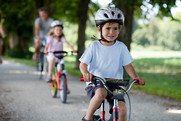 4 years old boy riding a bicyle in front of his family on a grav