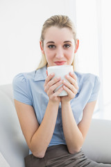 Gorgeous calm businesswoman holding a cup smelling a cup