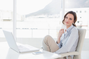 Businesswoman with laptop drinking coffee in office
