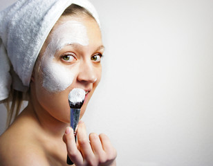 Young beautiful woman with clay facial mask on her face