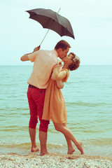 Summer vacation concept. Couple standing on beach and kissing