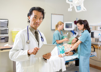 Doctor Using Digital Tablet While Nurses Treating Patient