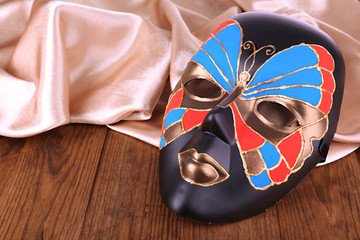 Mask on golden fabric on wooden background