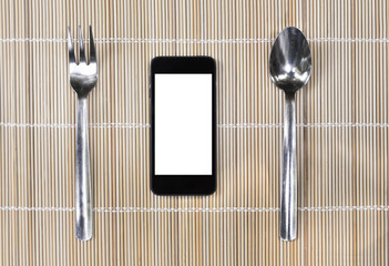 Smartphone with fork and spoon on bamboo mat background