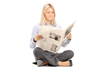Young smiling woman sittong on a floor and reading a newspaper