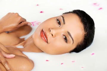 Wall Mural - Attractive naked woman lying in a milk bath. With rose petal. Up