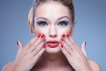 Wall Mural - surprised young beauty woman with fingers on her face
