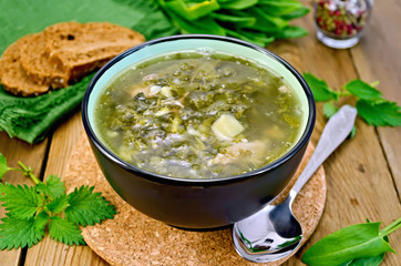 Soup green of sorrel and nettles with bread on the board