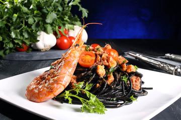 pasta nera con pesce e gamberi sfondo scuro