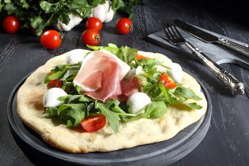 pizza bianca prosciutto e rucola sfondo grigio
