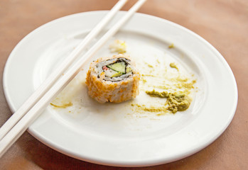 Sushi on a white plate with chopsticks