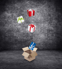 Gift boxes with colored ribbons fall in a large cardboard box.
