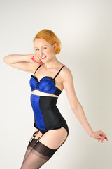 Retro red head in blue underwear and black stockings