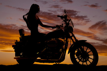 Silhouette of woman sitting on motorcycle
