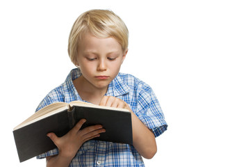 Young boy reading a thick book.