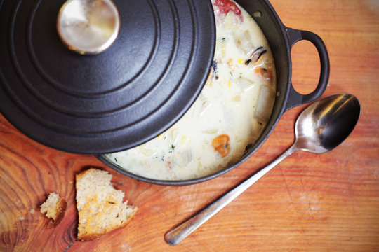 Clam chowder with sausage and potatoes in iron casserole