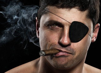 Portrait of a pirate with a cigar looking camera