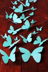 Paper blue butterflies on wooden board background