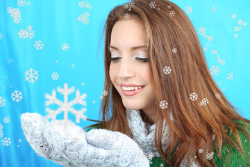 Beautiful smiling girl with snow on blue background