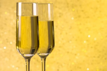 a pair of flutes of champagne golden abstract background