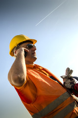 Worker with mobile phone antiphones and gloves