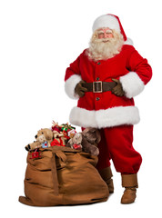 Santa Claus posing near a bag full of gifts