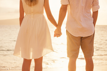 Couple holding hands at sunset on beach. Romantic young couple i