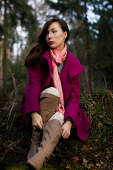 Well-dressed young woman in pink topcoat sitting in forest